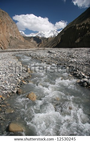 View on a clean mountain creek with Himalaya mountains in background. Annapurna trekking. Himalaya. Nepal - stock photo