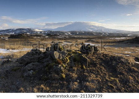 View on a frozen volcanic landscape with Hekla vulcan in background. - stock photo
