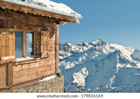 view on a snowy mountain and blue sky from a cottage - stock photo