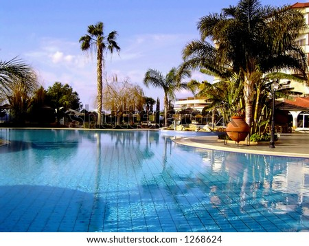 View on a swimming pool in exotic location (a holiday resort).