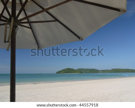 View on a tropical beach from underneath an umbrella