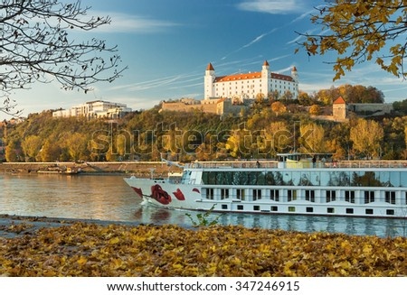 View on Bratislava castle,St. Martin´s cathedral and boat on river Danube in autumn,Slovakia - stock photo