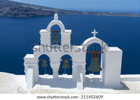 View On Calm Sea Surface Through Traditional Greek White Church Arch With Cross And Bells In Village Oia of Cyclades Island Santorini, Greece - stock photo
