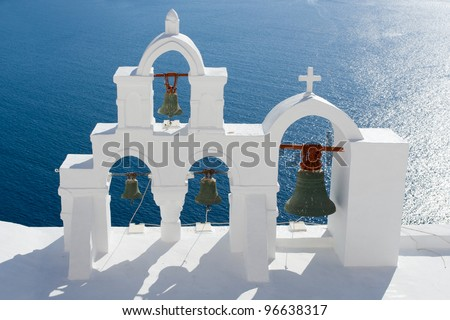 View on calm sea surface through traditional Greek white church arch with cross and bells in village Oia of Cyclades Island Santorini Greece - stock photo