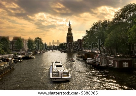 View on city canal (Amstel river) with cruise ship in Amsterdam, Netherlands (Holland). - stock photo