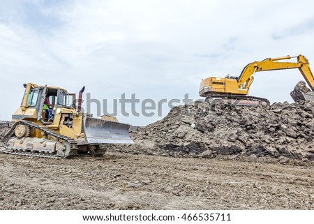 View on construction site with machinery, bulldozer is leveling construction site. Landscape transform into large urban area.