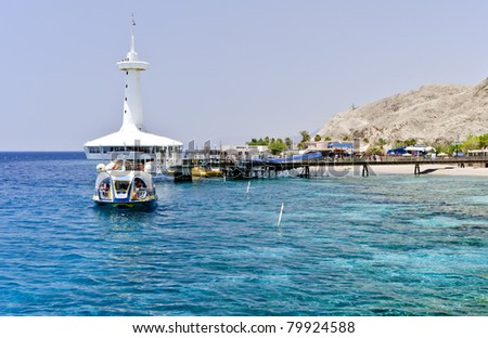 View on coral reef and building of underwater observatory near Eilat, Israel - stock photo