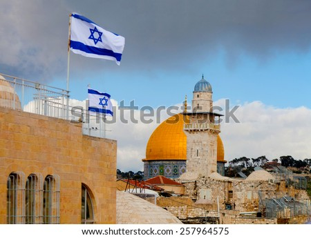 View on Dome of the Rock mosque in Jerusalem and Israeli flags from a balcony during a cloudy winter sunset (dramatic sky, evening lighting)  - stock photo