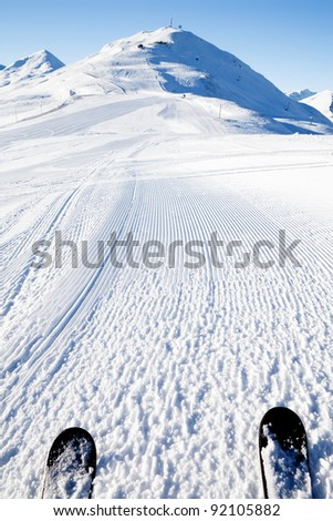 View on empty fresh-made downhill ski slope and mountains on a sunny day - stock photo