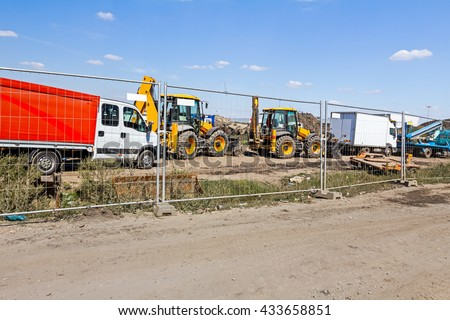View on few excavators through a fence wire, parked at construction site. - stock photo