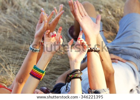 View on friends' raised hands outdoors, close-up - stock photo
