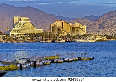 View on hotels, moored pleasure yachts and motor boats in marina of Eilat - popular resort and recreation city of Israel - stock photo