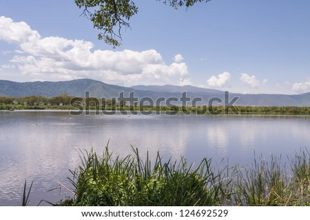 View on huge Ngorongoro caldera (extinct volcano crater) from within with large lake before against blue sky background. Great Rift Valley, Tanzania, East Africa.