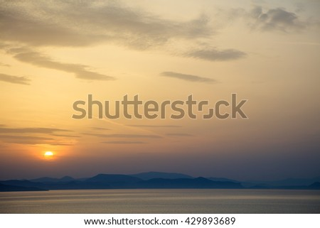 View on idyllic sunset at sea over mountains