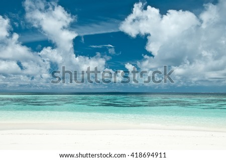 View on idyllic tropical beach with white sand, turquoise ocean water and blue sky with white clouds. - stock photo