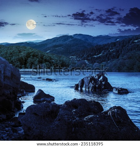 view on lake with rocky shore and some boulders near forest on mountain  with high vista far away at night in full moon light - stock photo
