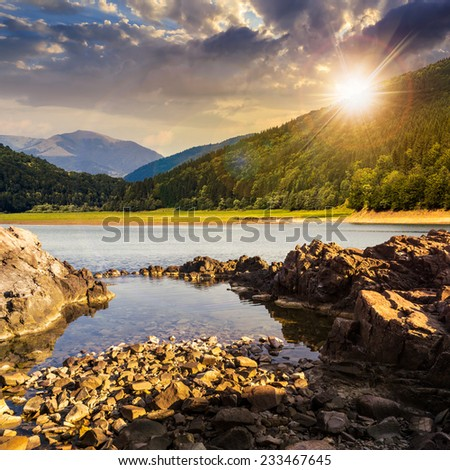 view on lake with rocky shore and some boulders near pine forest on mountain  with high vista far away at sunset - stock photo