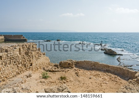 View on Mediterranean sea with fishers on remains of ancient harbor and ruins of antique wall and in foreground. Acre, Western Galilee region, Israel.
