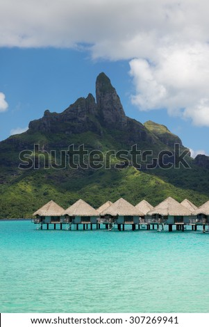 view on Mount Otemanu through turquoise lagoon and overwater bungalows on the tropical island Bora Bora, honeymoon destination, near Tahiti, French Polynesia, Pacific ocean - stock photo