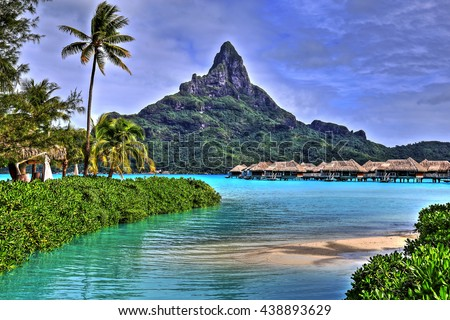 View on Mount Otemanu through turquoise lagoon, palms, and overwater bungalows on the tropical island Bora Bora, honeymoon destination, near Tahiti, French Polynesia, Pacific ocean. HDR picture. - stock photo