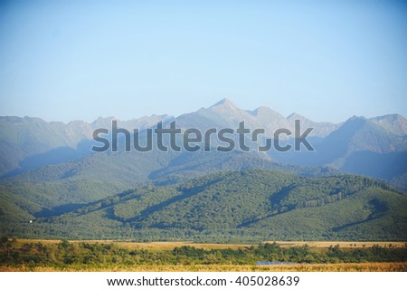 view on mountains and field at sunny day