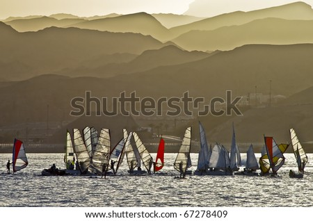view on mountains of Eilat and yachts at sunset during dust-storm, Israel - stock photo