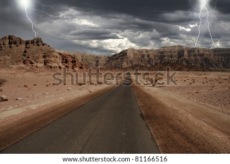 View on narrow road running through the mountains of Arava desert under the cloudy stormy sky with lightnings in Israel. - stock photo