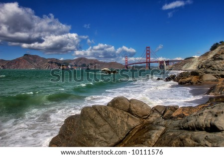 View on Pacific ocean, rocks and Golden Gate Bridge from Baker Beach in San Francisco, USA. - stock photo