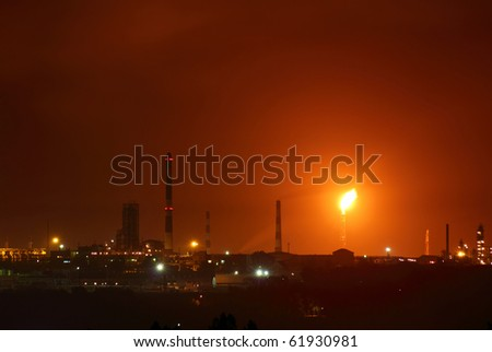 view on petrochemical factory with flame at night - stock photo