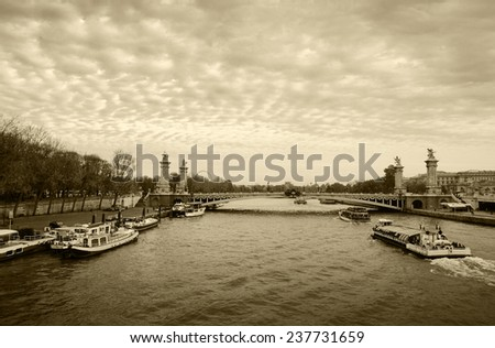 View on Pont Alexandre III (Alexander III Bridge) and tourist cruise ships in autumnal cloudy evening. Cloudscape. Paris, France. Aged photo. Sepia. - stock photo