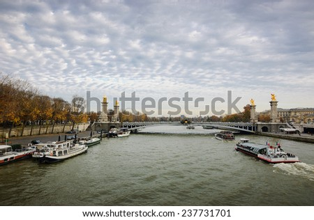 View on Pont Alexandre III (Alexander III Bridge) and tourist cruise ships in autumnal cloudy evening. Cloudscape. Paris, France.  - stock photo