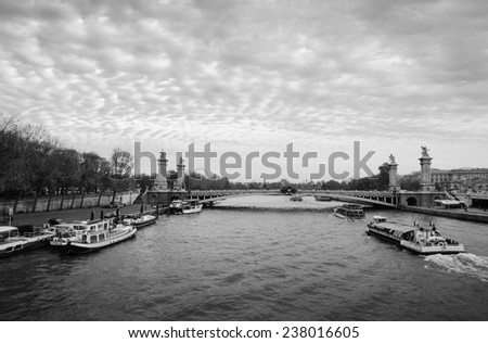 View on Pont Alexandre III (Alexander III Bridge) and tourist cruise ships in autumnal cloudy evening. Cloudscape. Paris, France. Aged photo. Black and white. - stock photo