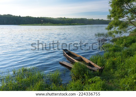 View on river with wooden boat laid up near gangway on riverbank. Noviny village, Arkhangelsky region, Russia.