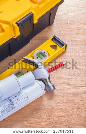 view on rolled up blueprints claw hammer level tool box on wooden board construction concept