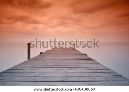 View on scenic seascape with wooden pier at sunset of red and orange colors - stock photo
