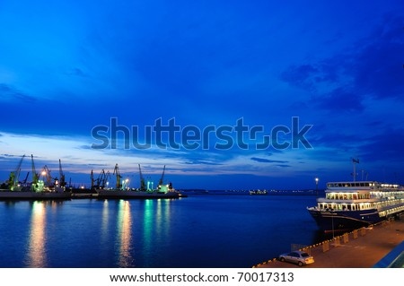 View on seaport with cranes, cargo and passenger ships at the night. - stock photo