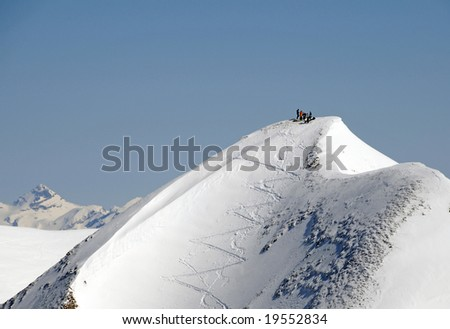 View on snow covered peak with five extreme skiers