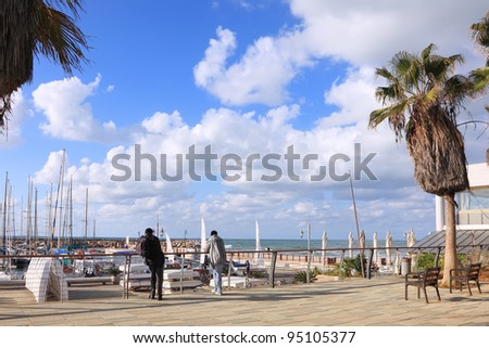 View on Tel-Aviv marina and Mediterranean sea and tourists standing on the wooden embankment. Israel
