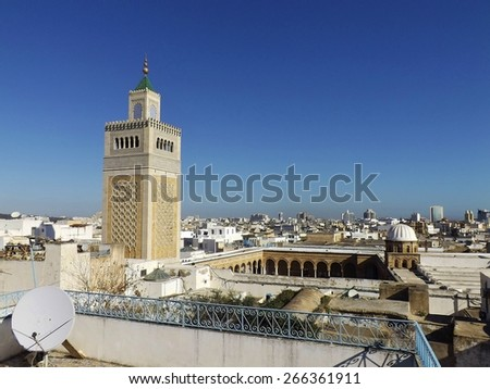 """View on the Al-Zaytuna Mosque and the skyline of Tunis. The mosque is a landmark of Tunis. In the background the modern buildings of the new City or """"ville nouvelle"""" - stock photo"""