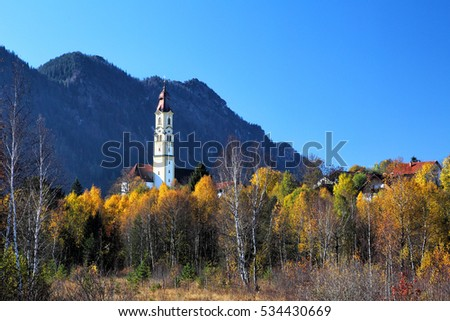 View on the autumn landscape at Pfronten, Bavaria, Germany in beautiful autumn weather with the Church St. Nikolaus in the foreground and the Kienberg in the background.