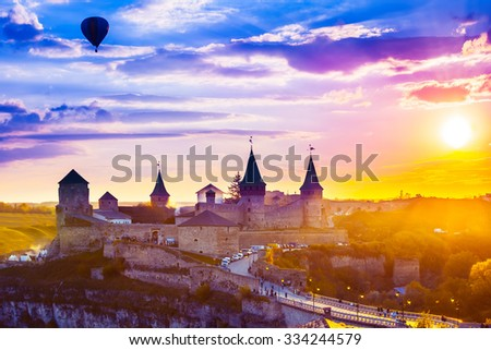 View on the castle in Kamianets-Podilskyi and red air balloon during sunset . Ukraine - stock photo