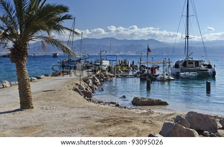 View on the gulf of Aqaba and pleasure touristic boats from the southern beach of Eilat, Israel - stock photo