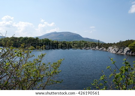 View on the mountain on the hot spring day over the calm lake with the view of mountains in the Killarney National Park in County Kerry in Ireland, May - stock photo