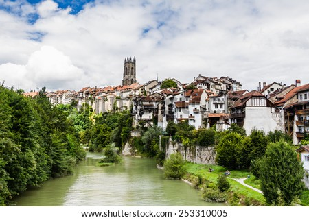 View on the Saane (Sarine) river and Cathedral of Saint Nicholas from Milieu bridge, Fribourg, Switzerland - stock photo