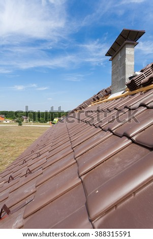 View on the tiled roof with chimneys from second floor of a new house - stock photo