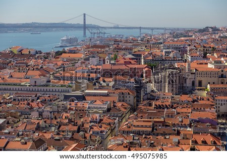 view on travel city Lisbon from top place of castle sao jorge. roofs, river tejo, brige 25 april, ships in summer day.
