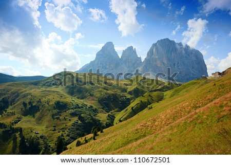 View on Tre Cime di Lamar from Passo Sella with alpine meadow on the foreground - stock photo