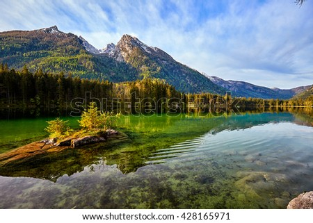 View on turquoise water and scene of trees on a rock island at Lake Hintersee.