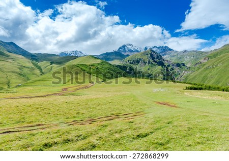 View on valley in Georgian mountains. Road with tire tracks to mountains and beautiful clouds - stock photo