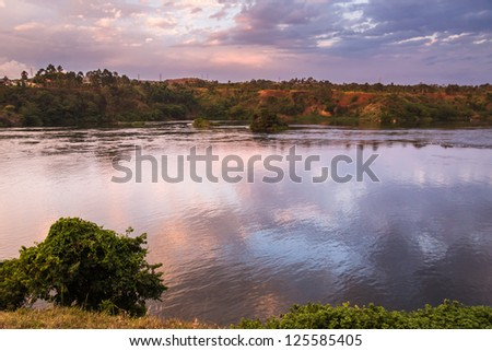 View on Victoria Nile River with island at dawn against sunrise glowing background. Jinja, Uganda, Eastern Africa.	 - stock photo